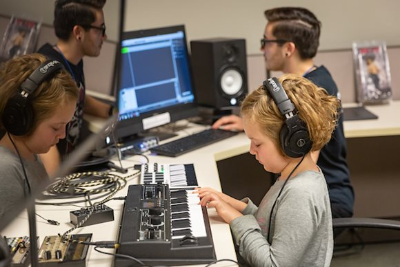 A young girl wears headphones and uses an electic keyboard to compose music