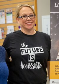 "[Image description: Amber Fawn Wooton Clark smiles while wearing a black and white T shirt that reads ""The Future is Accessible.]"